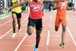 New Haven Connecticut - February 22, 2020: Caleb Owen of Wilbur Cross H.S. wins the boys 300-meter dash finals, center, crossing the finish line against third-place finisher Kymali Hay of Bloomfield H.S., right, and fourth-place finisher Rayshon Jacobs of Jonathan Law H.S, left. Jason Lorent of Shelton H.S. finished in second place. during the CIAC State Open Indoor Track Championship Saturday at the Floyd Little Athletic Center in New Haven.
