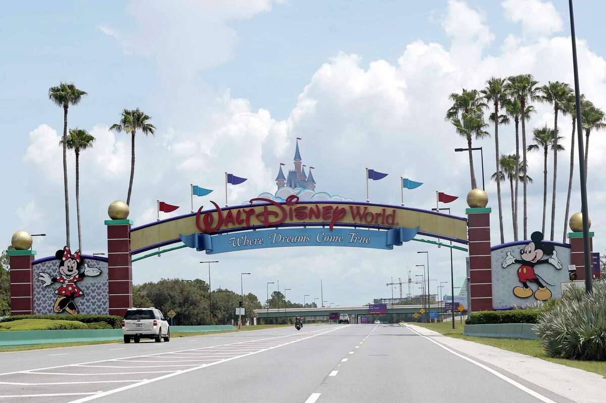 Cars drive under a sign greeting visitors near the entrance to Walt Disney World, Thursday, July 2, 2020, in Lake Buena Vista, Fla. Despite a huge surge of Floridians testing positive for the new coronavirus in recent weeks, Magic Kingdom and Animal Kingdom, two of Disney World's four parks are reopening Saturday, July 11. When they do, visitors to a€œThe Most Magical Place on Eartha€ will find new rules in place. (AP Photo/John Raoux)
