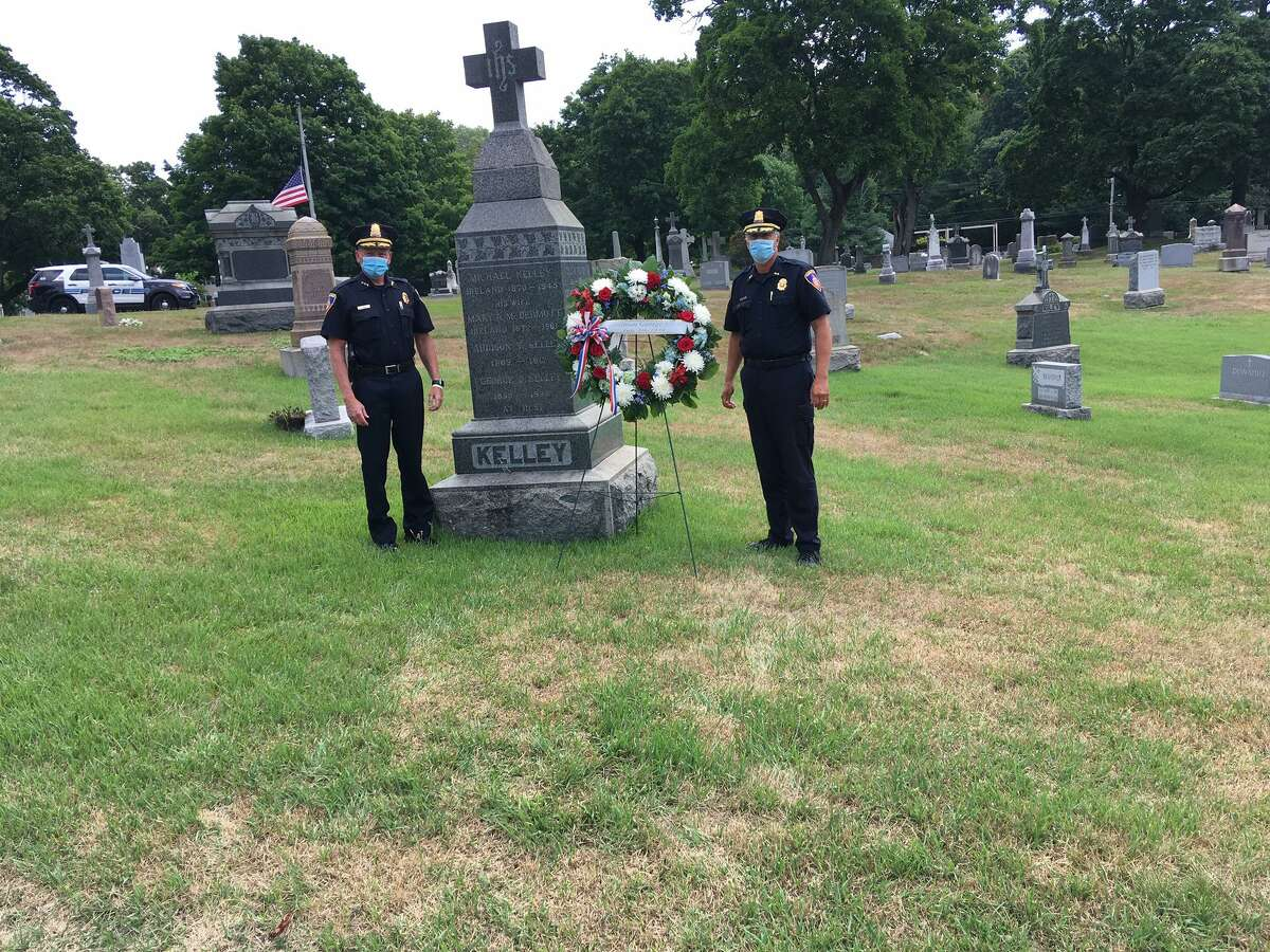 Stamford police Chief Tim Shaw, left, and Assistant Chief Tom Wuenneman place a wreath at the grave of the late police officer George Kelly, who died on July 8, 1938 in the line of duty.