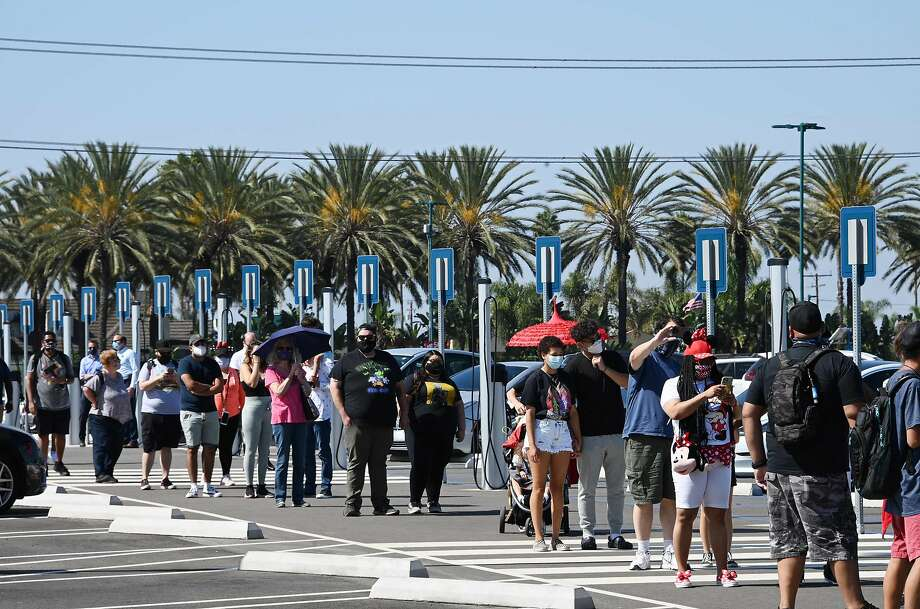 People wait in line to enter Downtown Disney in Anaheim, California on July 9, 2020, the first day the outdoor shopping and dining complex has been open to the public since it closed in mid-March amid the COVID-19 pandemic. Photo: Robyn Beck, AFP Via Getty Images