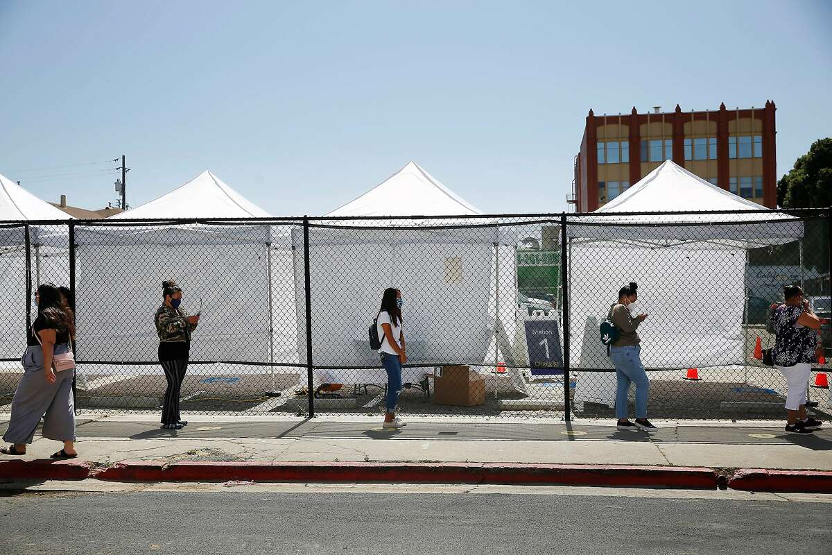 People line up for testing at the COVID-19 testing site at the Native American Health Center on Thursday, July 9, 2020 in Oakland, Calif.