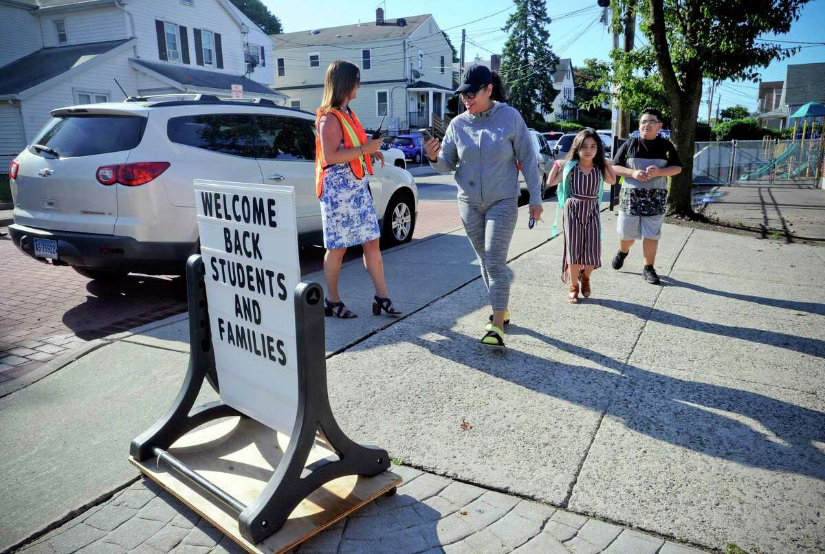 Principal Sherri Prendergast greets Anna Taroc and her children, Leyla Garcia and Chase Garcia as they arrive at KT Murphy School for the first day of school on August 29, 2019 in Stamford, Connecticut.