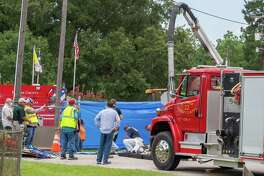 Emergency workers work outside a manhole to support responders in the tunnel below. Two men lost their lives while working underground in the sewer lines at the intersection of West Barkley and Mitchell Streets in Sour Lake on Thursday. Photo made on July 9, 2020. Fran Ruchalski/The Enterprise