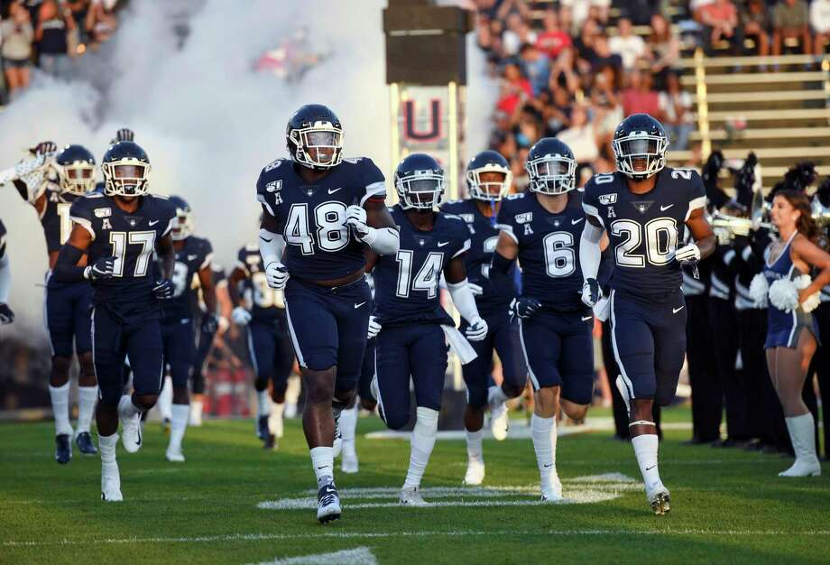 The UConn football team lost two games on its schedule Thursday when the Big Ten The Connecticut team heads out to the field at the start of the NCAA college football game against Wagner Thursday, Aug. 29, 2019, in East Hartford, Conn. (AP Photo/Stephen Dunn) Photo: Stephen Dunn / AP / Copyright 2019 The Associated Press. All rights reserved