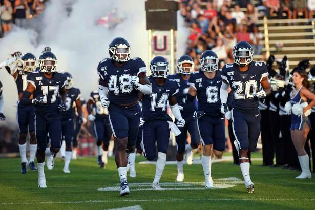 The UConn football team lost two games on its schedule Thursday when the Big Ten The Connecticut team heads out to the field at the start of the NCAA college football game against Wagner Thursday, Aug. 29, 2019, in East Hartford, Conn. (AP Photo/Stephen Dunn)