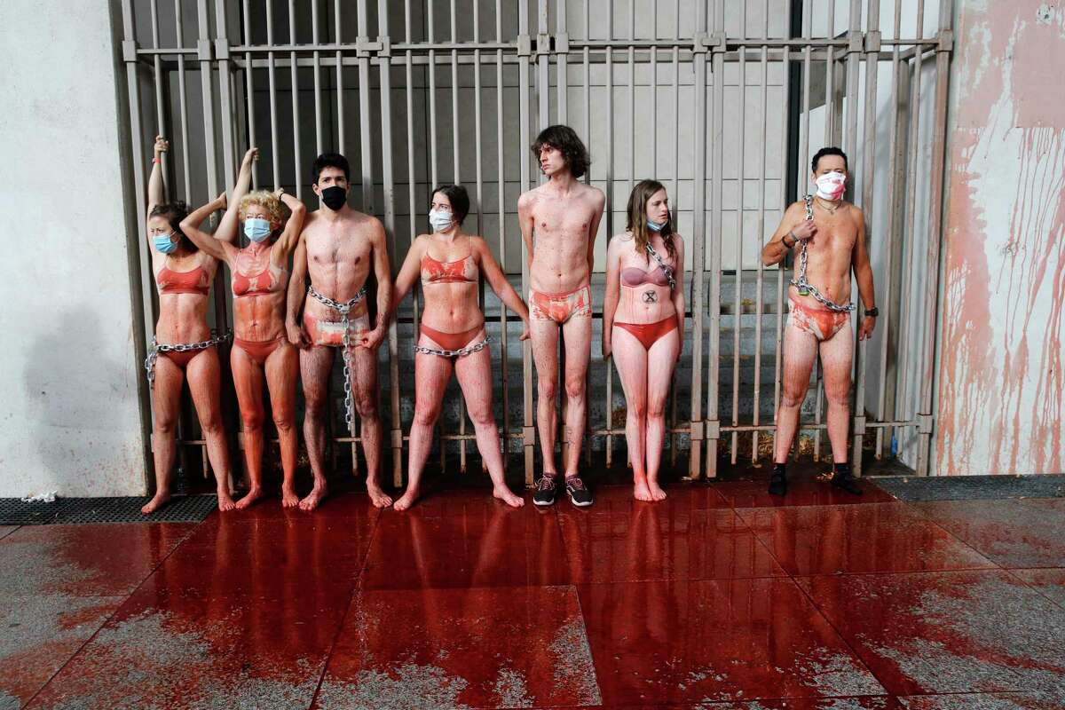 Environment activists of Extinction Rebellion (XR) chain themselves at a fence of the Economy Ministry after pouring fake blood on the ground, Tuesday, June 30, 2020 in Paris. French President Emmanuel Macron is under new pressure to fight climate change after the Green Party did well in Sunday's local elections.