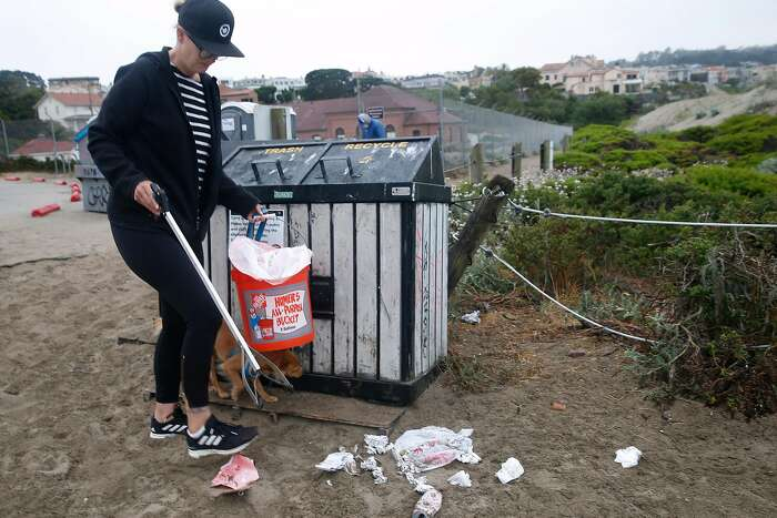 Eva Holman picks up trash and debris left behind by the previous day's visitors in front of the waste bins at Baker Beach in San Francisco, Calif. on Tuesday, June 23, 2020.