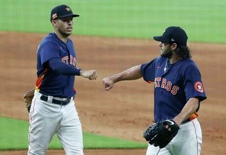With high-fives discouraged in 2020, Astros shortstop Carlos Correa, left, and pitcher Lance McCullers Jr. practiced their fist-bumping during Thursday's intrasquad scrimmage at Minute Maid Park.