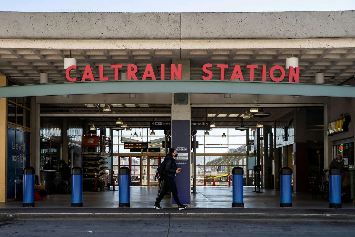 A woman walks past an entrance of the Caltrain Station at King Street and 4th Street on Thursday, July 9, 2020, in San Francisco, Calif. California rolled out its vision for high-speed trains between San Jose and San Francisco on Thursday, plotting a 30 or so minute ride on what would be one of the busiest stretches of the state�s proposed 520-mile rail system. The California High Speed Rail Authority is calling for 220-mph trains, coming from the Central Valley, to merge onto the Caltrain commuter line for a 49-mile jaunt up the Peninsula. Stops would be made at San Jose�s Diridon Station, a new hub in Millbrae and at the Caltrain depot in San Francisco. The San Francisco stop would eventually move to Transbay transit center.