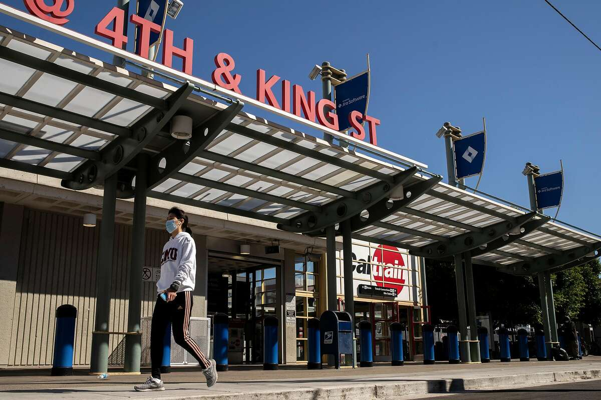 A person walks past the Caltrain Station at King Street and 4th Street on Thursday, July 9, 2020, in San Francisco, Calif. California rolled out its vision for high-speed trains between San Jose and San Francisco on Thursday, plotting a 30 or so minute ride on what would be one of the busiest stretches of the state�s proposed 520-mile rail system. The California High Speed Rail Authority is calling for 220-mph trains, coming from the Central Valley, to merge onto the Caltrain commuter line for a 49-mile jaunt up the Peninsula. Stops would be made at San Jose�s Diridon Station, a new hub in Millbrae and at the Caltrain depot in San Francisco. The San Francisco stop would eventually move to Transbay transit center.