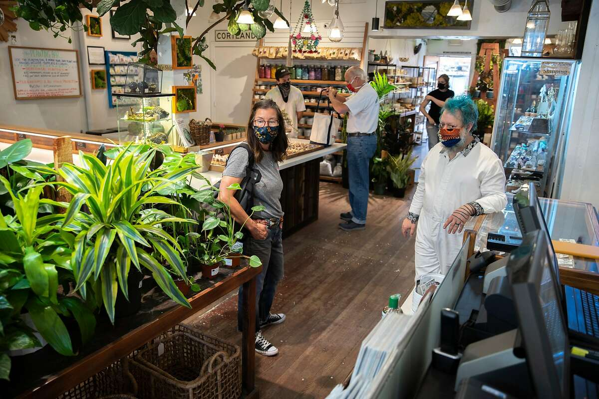 From left: Heather Ramsey gets plant care tips from business owner Ken Shelf at Succulence on Thursday, July 9, 2020, in San Francisco, Calif. Ramsey was looking for a house plant to decorate her spouse�s home office. The coronavirus pandemic has forced Ramsey to leave home only for essentials and has developed a houseplant hobby.