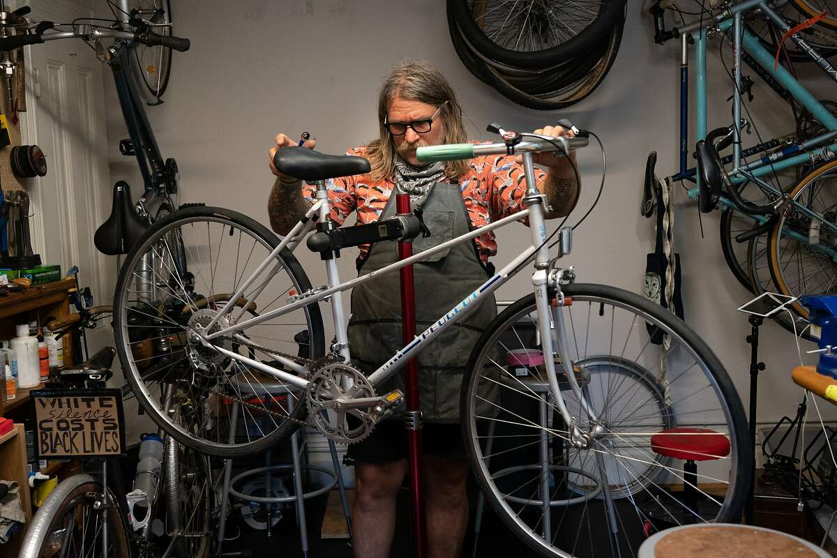 Jay Beaman working on a 40-year-old bike in his converted dining room as he hopes to get more bicyclists on the road - and more people eager for a future San Francisco that puts bikes over cars on Wednesday, July 8, 2020 in San Francisco, Calif.