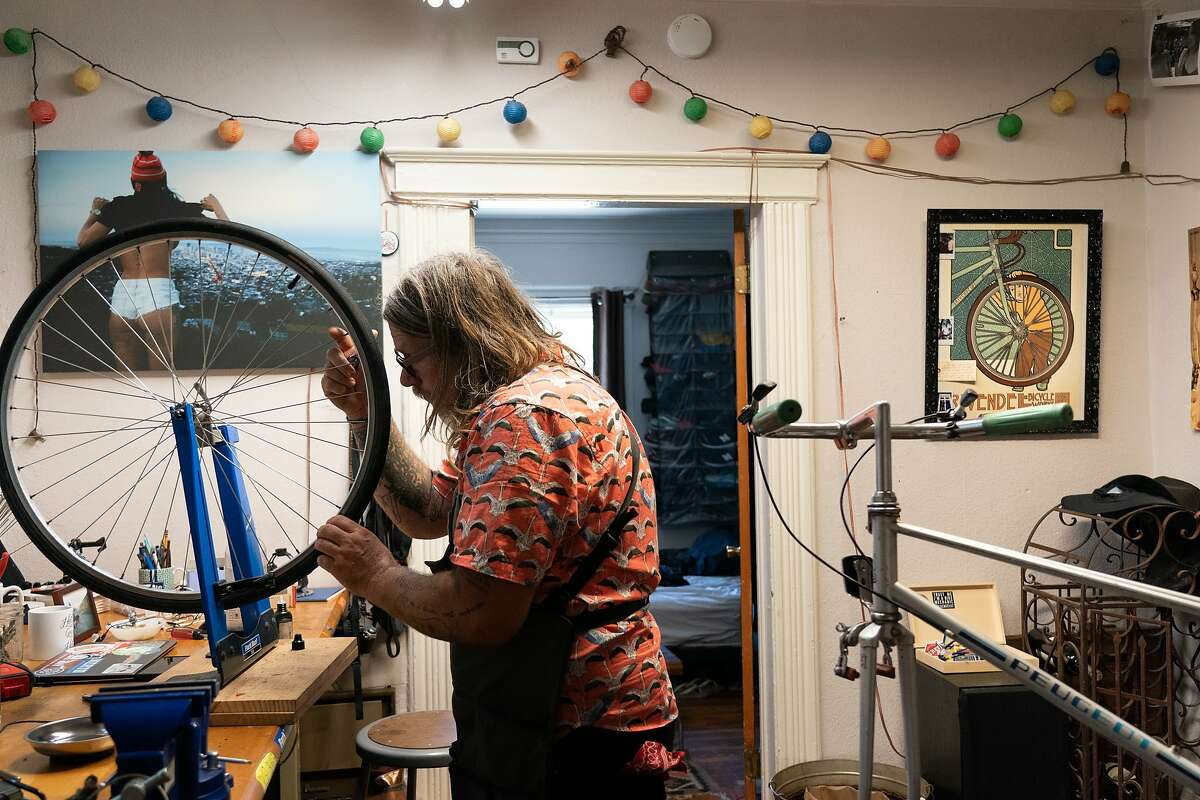 Jay Beaman trues a wheel in his converted dining room as he hopes to get more bicyclists on the road - and more people eager for a future San Francisco that puts bikes over cars on Wednesday, July 8, 2020 in San Francisco, Calif.