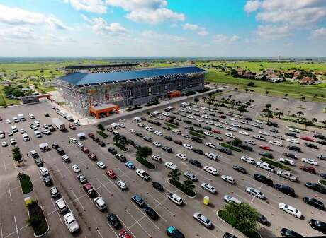 People line up for COVID-19 tests in the parking lot of H-E-B Park soccer stadium in Edinburg on Thursday. The federally run testing site will continue testing patients at Bert Ogden Arena through July 14. Pre-registration is required.