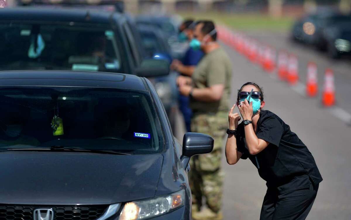 A member of the Texas National Guard shows a motorist how to use the self-administered COVID-19 swab in the H-E-B Park soccer stadium's parking lot in Edinburg on Thursday. Federal health officials have established a temporary testing site at Bert Ogden Arena with the goal of swabbing 5,000 patients a day through July 14. Pre-registration is required.