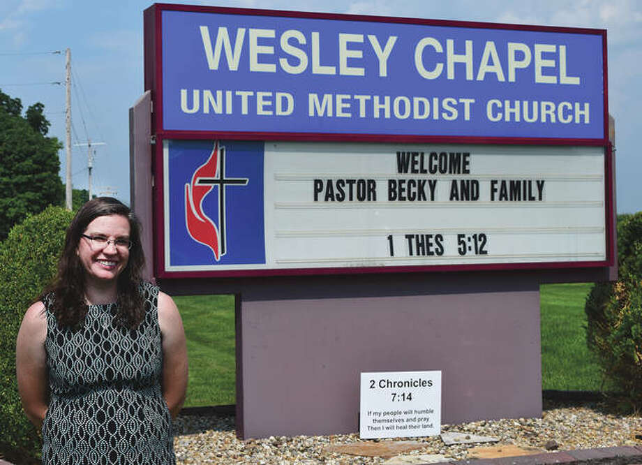 The Rev. Rebecca Williams stands in front of the Wesley Chapel United Methodist Church sign that displays a welcoming message. Photo: Rochelle Eiselt | Journal-Courier