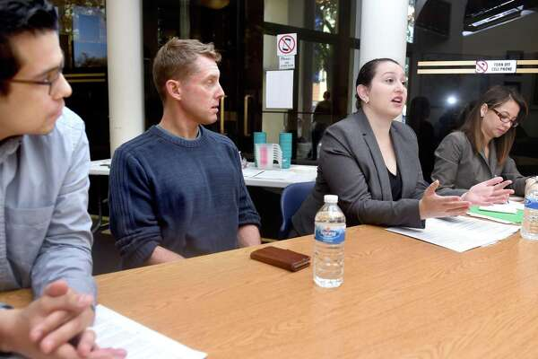 Left to right, Melvin Medina, Advocacy and Outreach Director for the ACLU of Connecticut, and Dan Barrett, Legal Director of the ACLU of Connecticut, listen to attorney Ellen Messali of New Haven Legal Assistance speak about how to interact with police during a discussion at the Consulate General of Ecuador in New Haven in 2016. At right is Cristina Velasquez acting as an interpreter.