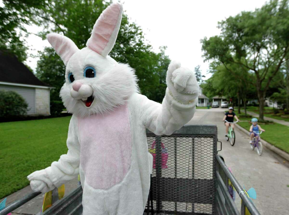 Michael Bisbee, dressed as the Easter Bunny, dances as a family rides beside him as his family drives around neighborhoods in The Woodlands to spread some Easter joy, Friday, April 10, 2020. Bisbee, 55, passed away unexpectedly on Monday.