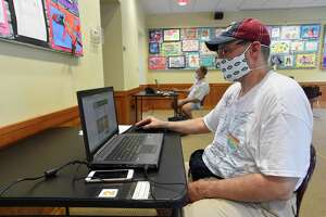 Byram resident James Santora uses a computer on July 9, 2020 at the Byram Shubert Library in Greenwich, Connecticut to gather and print out a script for a play he planned to audition for a role in. The library has begun to allow a limited number of residents inside to use the computers, but not to browse for books. Computers are spaced six feet apart, face coverings and social distancing are required at all times.