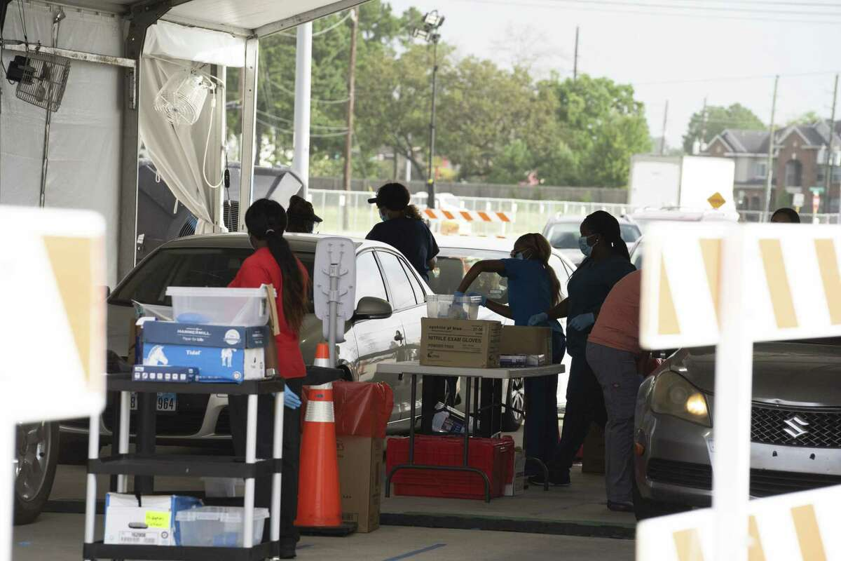 Medical workers wearing protective masks and gloves preform a Covid-19 tests at a Harris County drive-thru testing site at Ken Pridgeon Stadium in Houston, Texas, U.S., on Wednesday, July 1, 2020. Anthony Fauci, the U.S. government's top infectious disease specialist, warned lawmakers that coronavirus infections could rise to100,000 a dayif behaviors don't change. Photographer: Go Nakamura/Bloomberg
