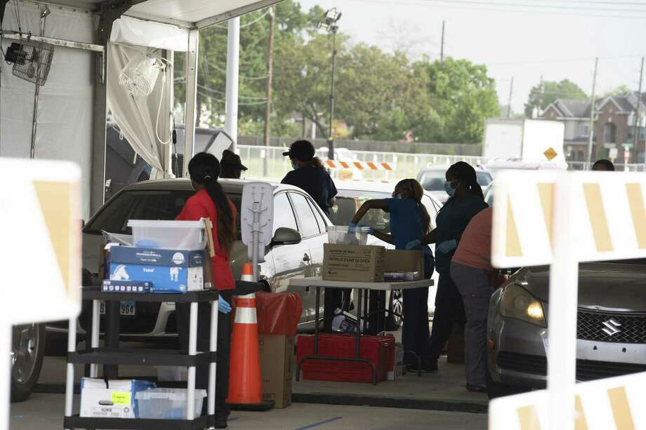 Medical workers wearing protective masks and gloves preform a Covid-19 tests at a Harris County drive-thru testing site at Ken Pridgeon Stadium in Houston, Texas, U.S., on Wednesday, July 1, 2020. Anthony Fauci, the U.S. government's top infectious disease specialist, warned lawmakers that coronavirus infections could rise to100,000 a dayif behaviors don't change. Photographer: Go Nakamura/Bloomberg Photo: Go Nakamura / Bloomberg / © 2020 Bloomberg Finance LP
