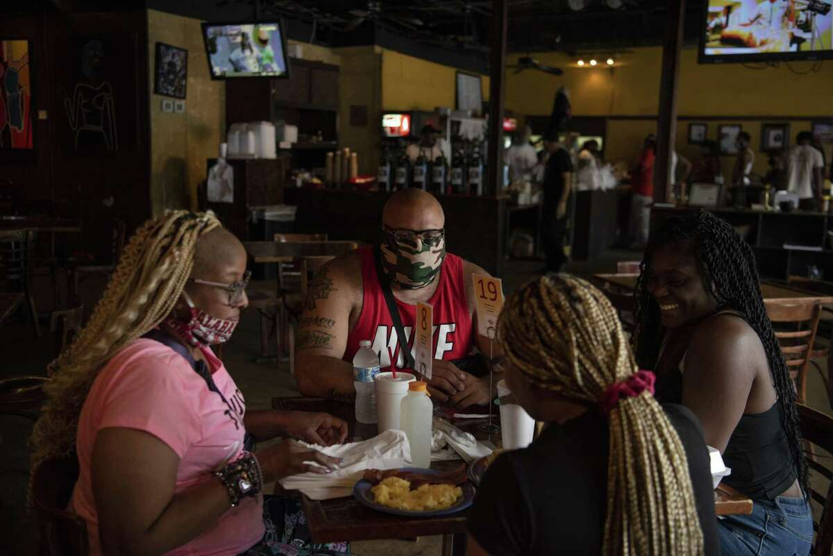 People wearing protective masks eat at a restaurant in Houston on Saturday, June 27.