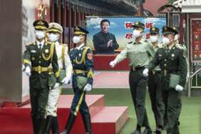 Members of the People's Liberation Army honor guards walk past a banner depicting Chinese president Xi Jinping near the Forbidden City in Beijing on May 21, 2020.
