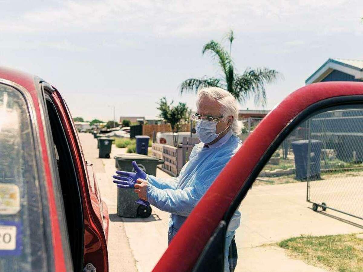 "Dr. Ricardo Cigarroa makes a house call in Laredo's Cuatro Vientos neighborhood. He has dubbed his Toyota Tacoma ""The COVID-mobile."""