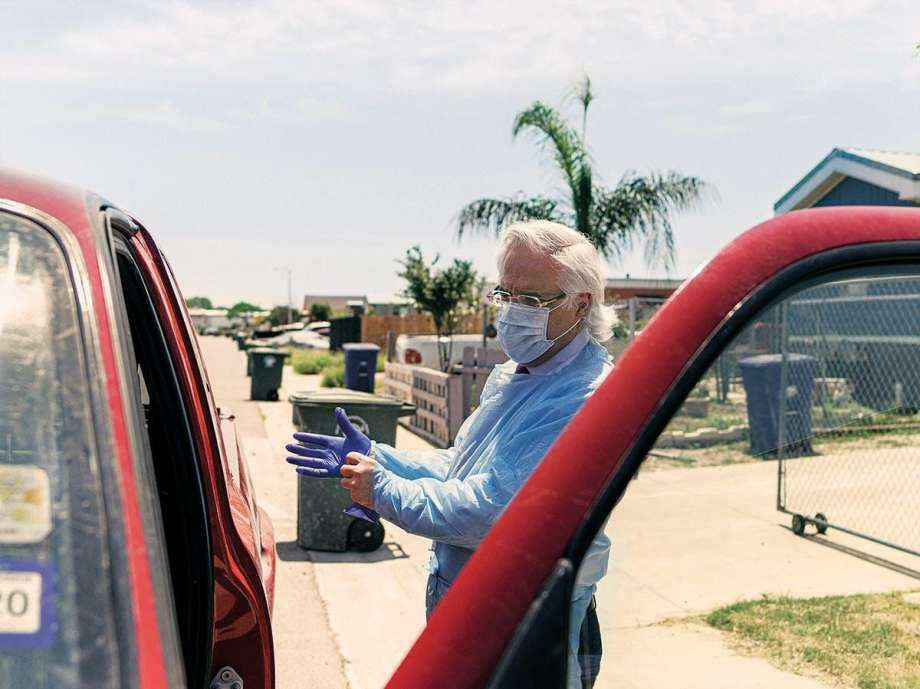 "Dr. Ricardo Cigarroa makes a house call in Laredo's Cuatro Vientos neighborhood. He has dubbed his Toyota Tacoma ""The COVID-mobile."" Photo: Josh Huskin /Texas Montly"