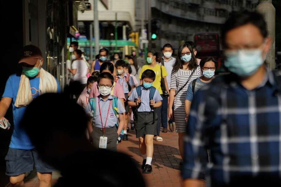 Pedestrians and schoolchildren wearing masks walk along a sidewalk in Hong Kong on July 10, 2020. A surge in coronavirus cases after a long stretch without infections is forcing the financial hub to reinstate restrictions that had been loosened. Photo: Bloomberg Photo By Roy Liu / Bloomberg