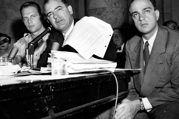 Senator Joe McCarthy is seen here waving a transcript of a monitored call between Pvt. G. David Schine (L) and Army Secretary Stevens, during the Army-McCarthy hearings, June 7, 1954 in Washington D.C. Schine appeared to listen to the transcript as it was read into the record. On the right is McCarthy's chief counsel, Roy Cohn. (Photo by APA/Hulton Archive/Getty Images)
