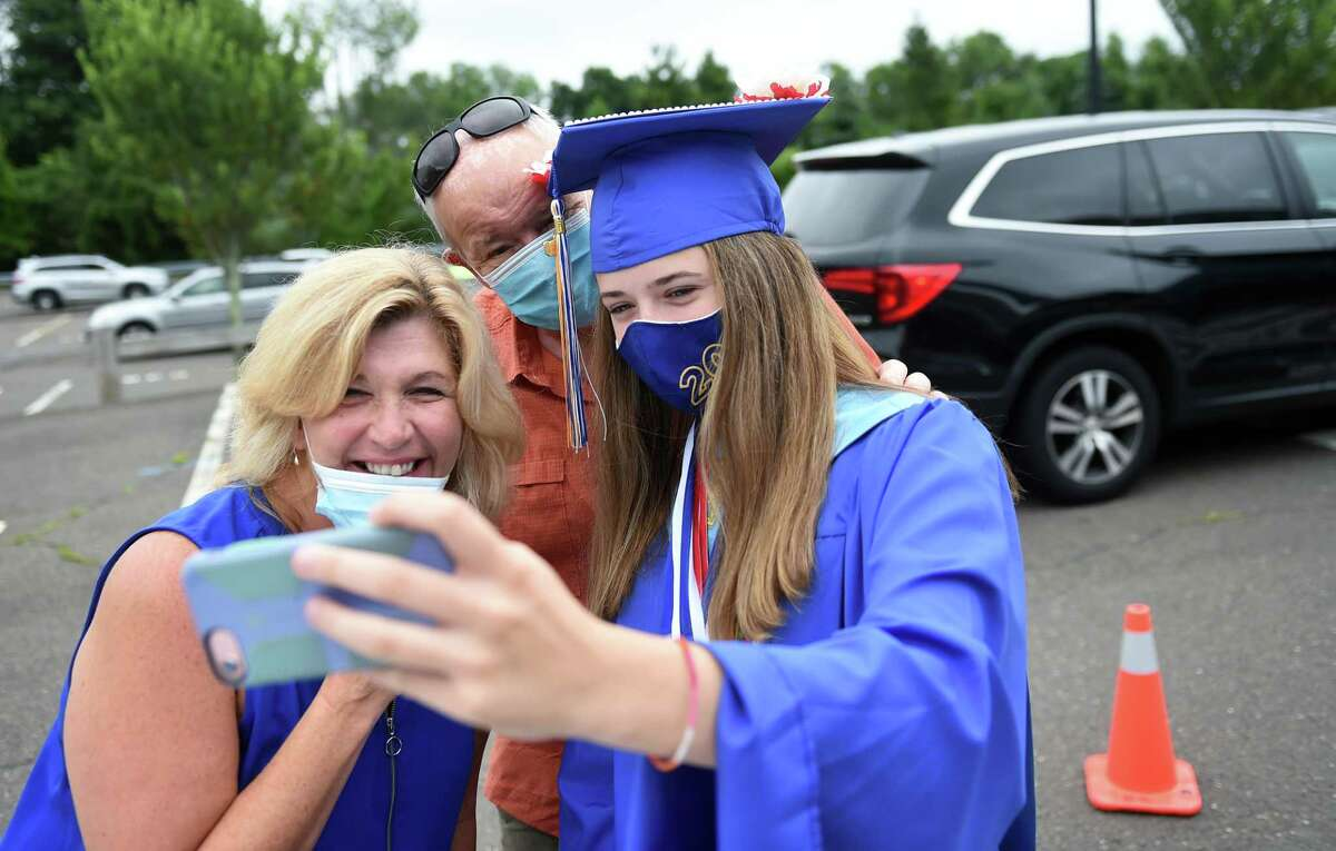 McKenzie Collins (right) takes a selfie with her parents, Lisa and William, during a drive thru graduation ceremony at Seymour High School on July 10, 2020.