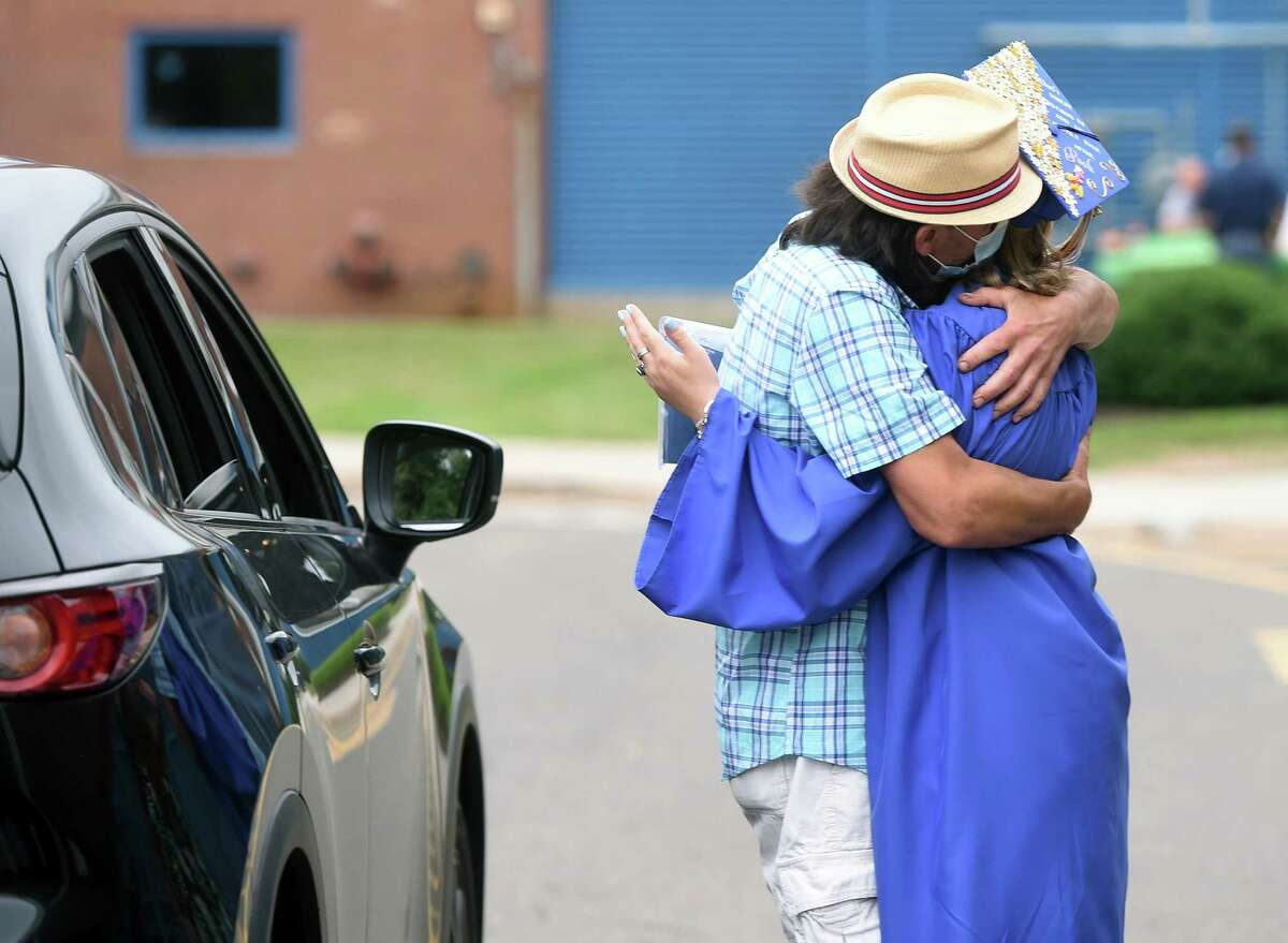 Class Speaker Grace Rennison gets a hug from her father, Tim, during a drive thru graduation ceremony at Seymour High School on July 10, 2020.