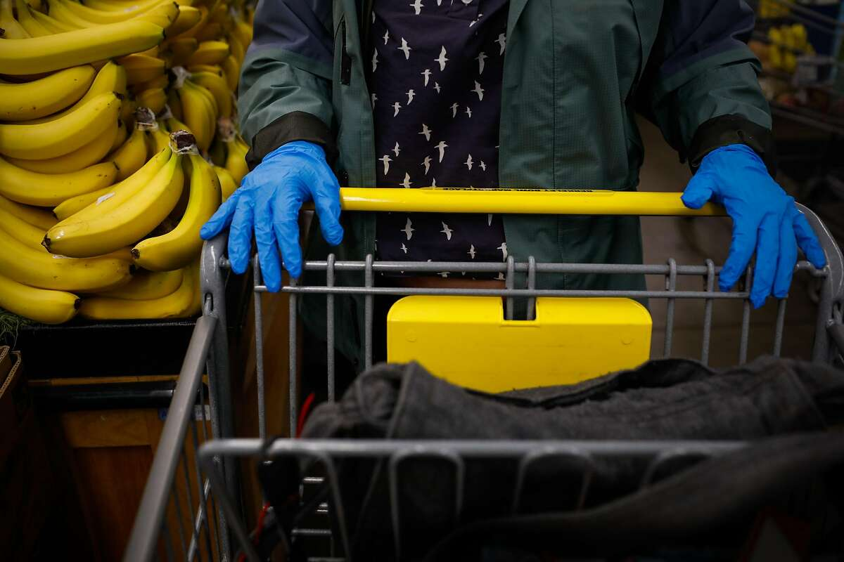 Oakland resident Shannon Ratay wears gloves as she shops for food for people in need at Berkeley Bowl on Sunday, March 15, 2020 in Berkeley, California. Ratay shopped for people who were in need of food but could not leave their house due to the coronavirus.