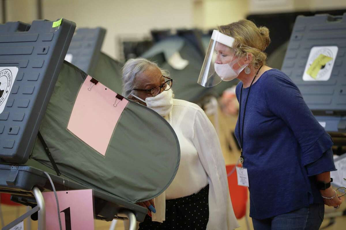 A.J. Official Marcia Ferguson (right) wears a plastic shield and face covering as she helps an early voter at in the Metropolitan Multi-Services Center, 1475 W Gray St., Monday, June 29, 2020, in Houston.