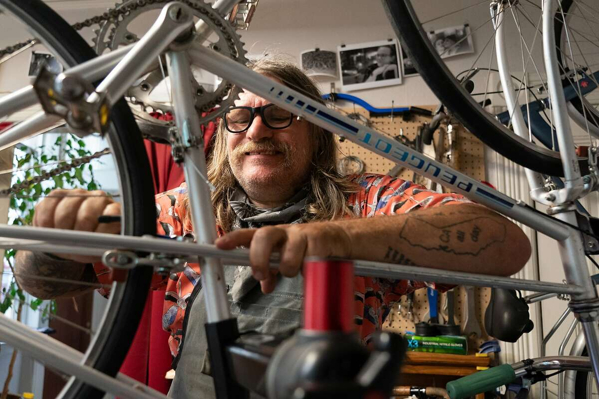 Jay Beaman grimaces as he loosens a bolt on a 40-year-old bike in his converted dining room as he hopes to get more bicyclists on the road - and more people eager for a future San Francisco that puts bikes over cars on Wednesday, July 8, 2020 in San Francisco, Calif.