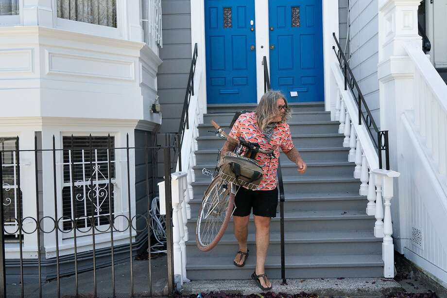 Jay Beaman carries one of his bikes out to ride on Wednesday, July 8, 2020, in San Francisco, Calif. Beaman repairs bikes for others in hopes to encourage biking over driving cars. Photo: Paul Kuroda / Special To The Chronicle