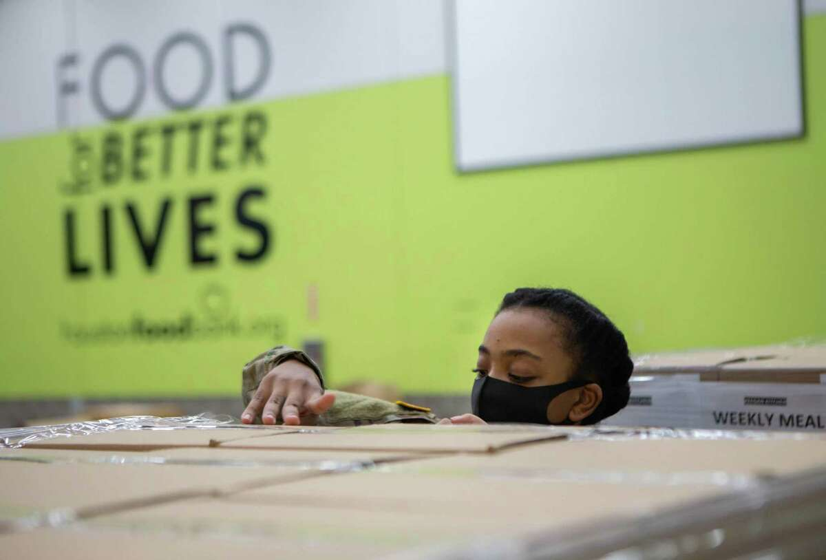 Private First Class, Ashia Byers, secures boxes of packaged food to be distributed. Because of the decrease in volunteers due to social distancing requirements, the National Guard has been instrumental in their help at the food bank. Next week they will be phased out, leaving administrators with concerns on how they will meet the high demand for food.