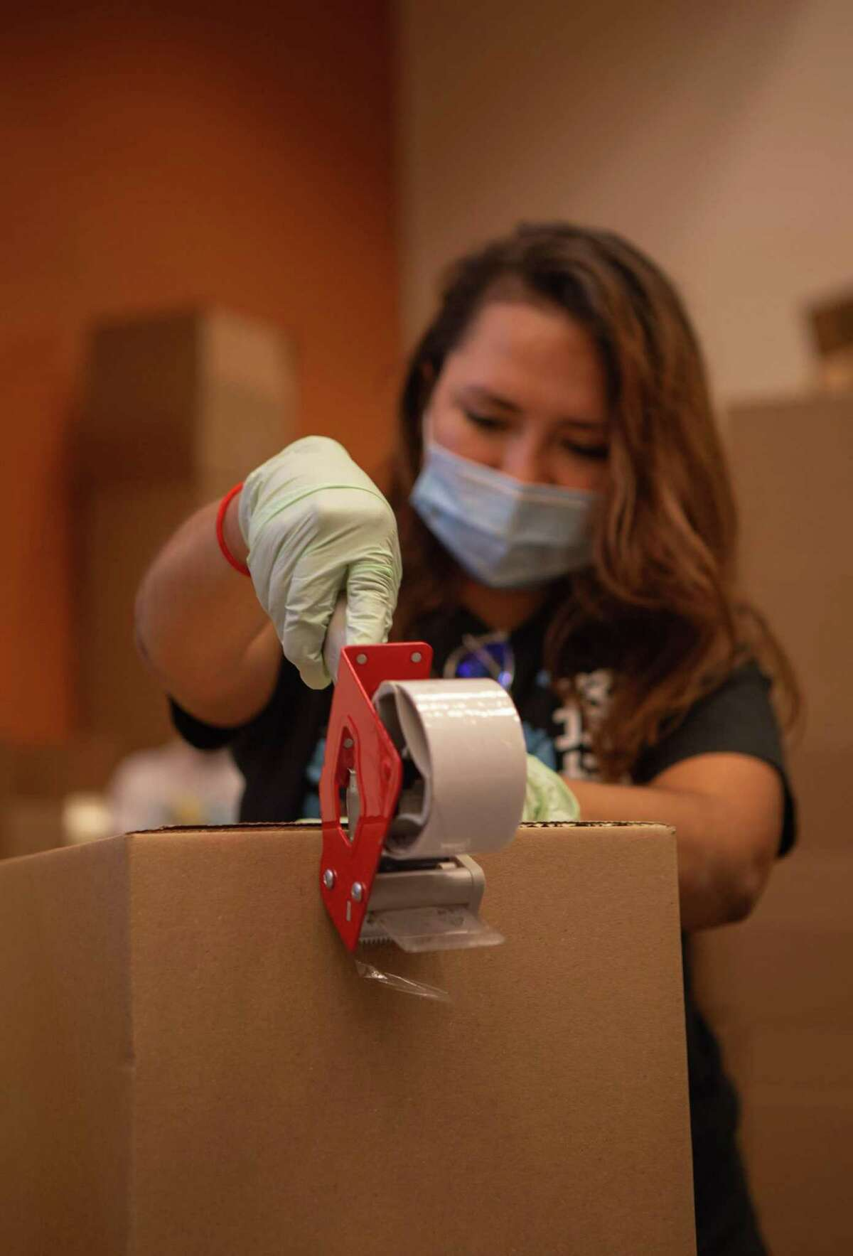 Volunteer, Ivania Escobar, 23, puts together boxes at the Houston Food Bank on Thursday, July 9, 2020. Volunteers now work in staggered shifts and are required to wear face-masks to prevent the spread of the coronavirus.
