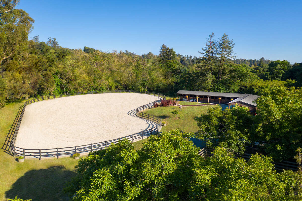 The property includes a professionally-designed main barn, pasture barn and expansive riding trails.