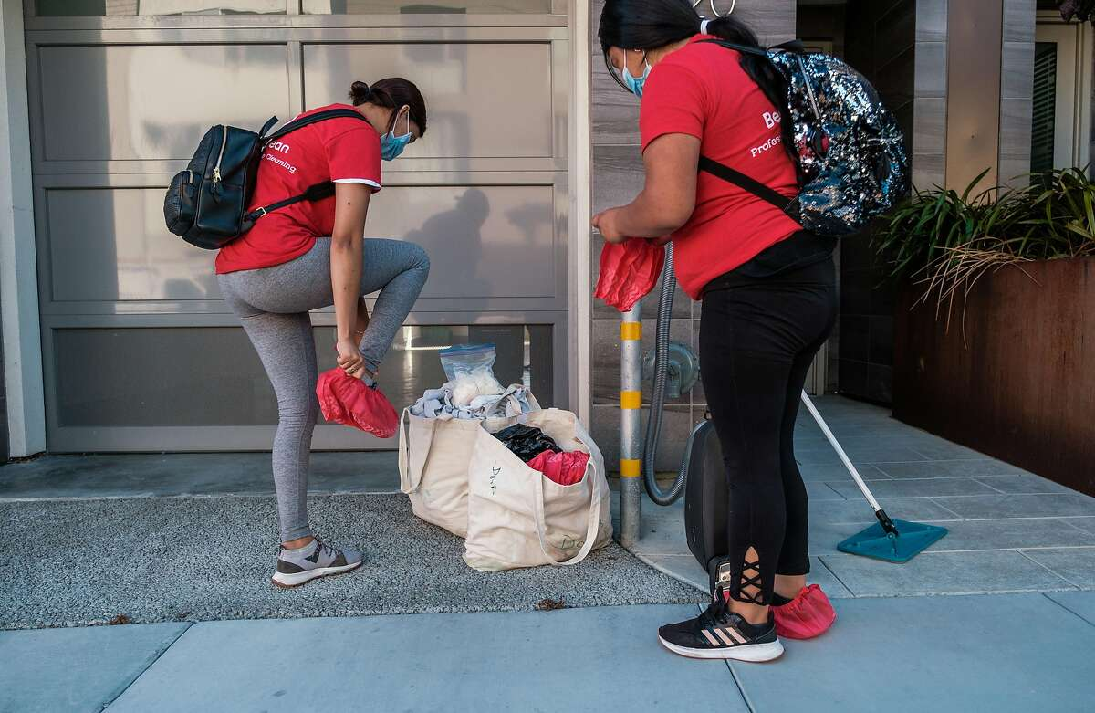 Jackie Mendez and Doris Chun, employees with BerryClean, don gloves and shoe coverings before entering a building to clean in San Francisco on Friday, July 10, 2020.