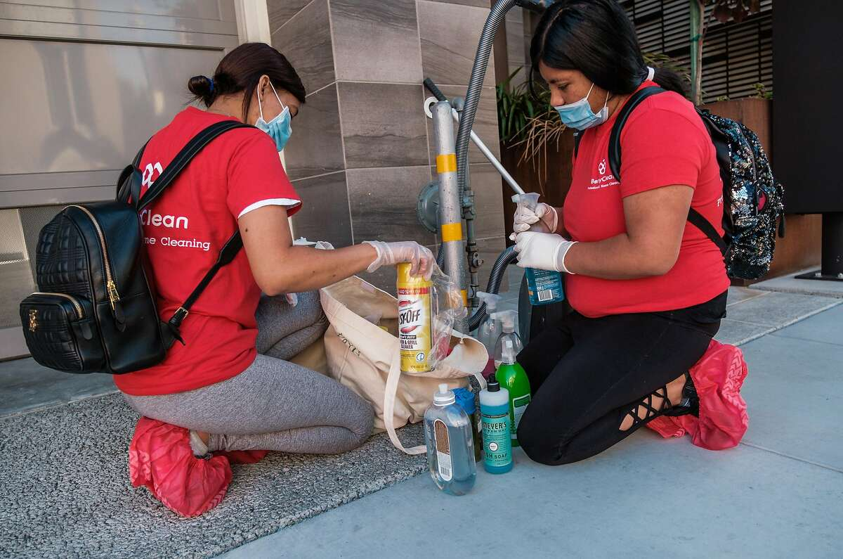 Jackie Mendez and Doris Chun, employees with BerryClean, prepare their cleaning items before entering a building to clean in San Francisco on Friday, July 10, 2020.