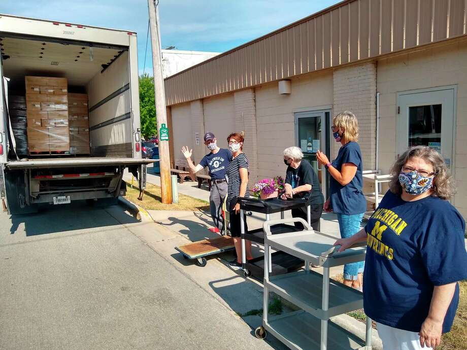 Manistee Senior Center staff and volunteers help unload boxes of fruits and veggies for Friday's produce distribution. Boxes for over 200 senior families were provided by Hereen Brothers of Comstock Park, which are working with the USDA to supply fresh fruits and vegetables to those in need. (Courtesy photo)