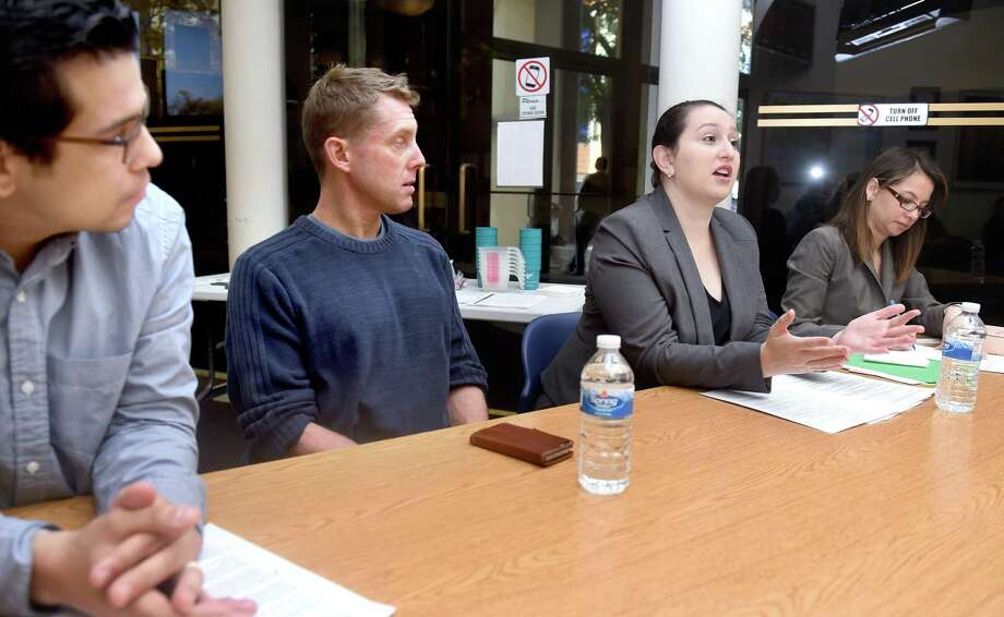 Left to right, Melvin Medina, Advocacy and Outreach Director for the ACLU of Connecticut, and Dan Barrett, Legal Director of the ACLU of Connecticut, listen to attorney Ellen Messali of New Haven Legal Assistance speak about how to interact with police during a discussion at the Consulate General of Ecuador in New Haven in 2016. At right is Cristina Velasquez acting as an interpreter. Photo: Arnold Gold / New Haven Register