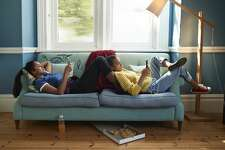 Women using mobile phones while relaxing on sofa in living room at home