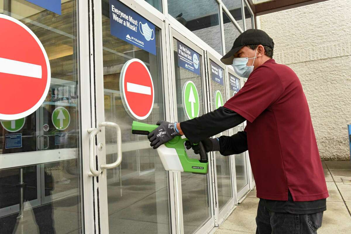 A mall employee disinfects the door handles inside and out as Crossgates Mall reopened public spaces on Friday July 10, 2020 in Guilderland, N.Y. Local malls can open their interior public spaces after the governor gave the go-ahead if the HVAC system meets certain standards for filtering out Covid-19. (Lori Van Buren/Times Union)