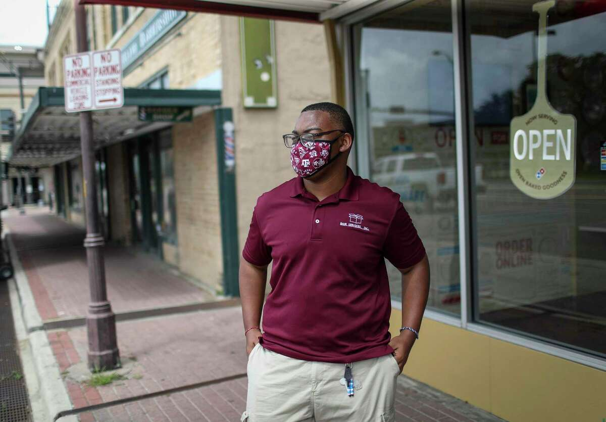 """Joseph Collins stands at the spot on University Drive at Texas A&M where he said a man yelled a racial slur at him from a passing car last month. """"Does he care that I'm a human being behind the flesh boundary that is my skin?"""" Collins said."""