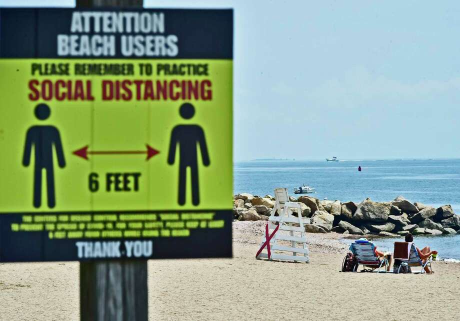A sign reminds visitors of social distancing measures at the town beach in East Haven Wednesday. Photo: Peter Hvizdak / Hearst Connecticut Media / New Haven Register