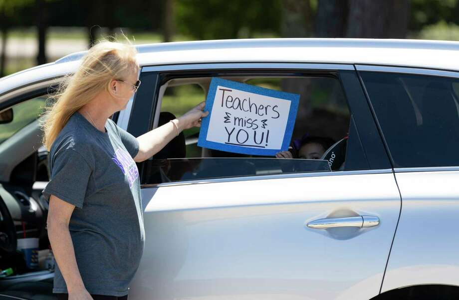 A child holds a sign displaying 'teachers we miss you,' outside Brabham Middle School in Willis, Thursday, April 23, 2020. The parade will take place over two days and involve a majority of faculty and staff. Photo: Gustavo Huerta, Houston Chronicle / Staff Photographer / Houston Chronicle © 2020