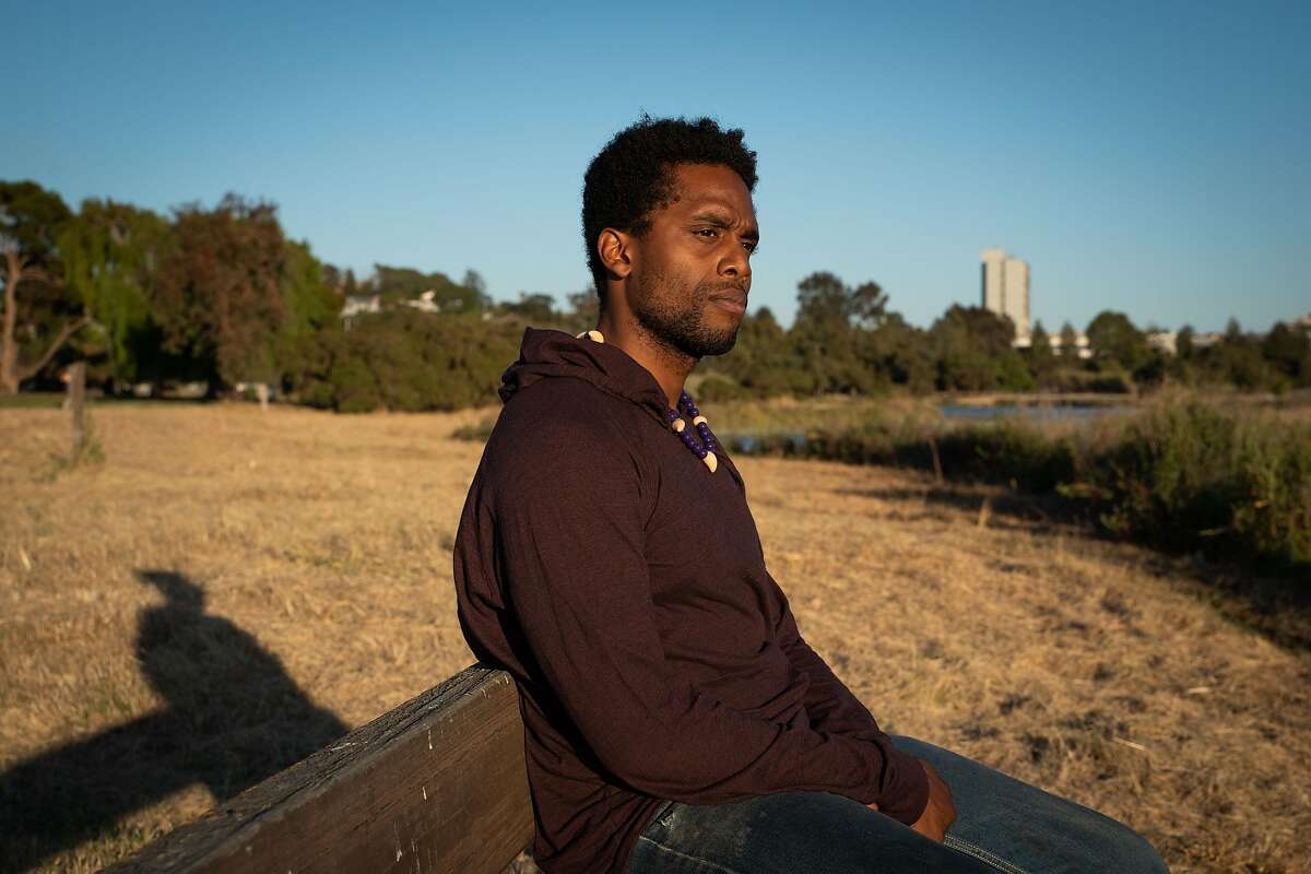 """Jeremy Malvo, 27, an Army veteran and physician assistant, poses for a photo at the marina in Martinez, Calif., on Thursday, July 9, 2020. """"You have to expect opposition,"""" said Malvo. """"When I came to America it was a whole different perspective. I was an Air Force brat � so I was born in England, moved to Japan then when I was 10, I moved to the States. Everywhere before living here, I was (considered) African. Then when I came here I was Black. There is a lot of rooted history here. People just need to come together. There are times when I'm like, I don't think I can go outside right now because the way things are."""""""
